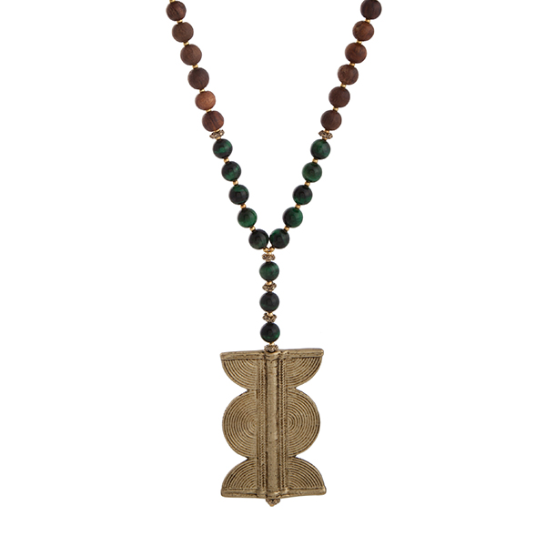 """Burnished gold tone half beaded necklace displaying green and brown wood beads with a 2 1/2"""" gold tone pendant. Approximately 35"""" in length. Handmade in the USA."""