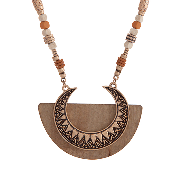 "Burnished gold tone bohemian style necklace with orange and natural beads and a crescent shaped pendant on light brown wood. Approximately 29"" in length."