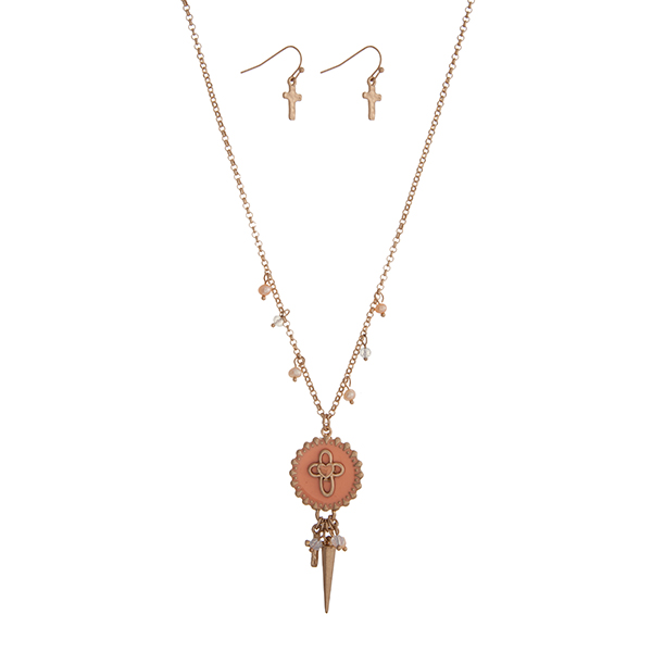 "Gold tone necklace set displaying a peach cross disk with a cluster of beads, a cross charm, and a spike. Approximately 18"" in length."