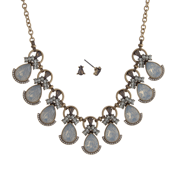 "Worn gold tone necklace set displaying white opal teardrop shape cabochons surrounded by clear rhinestones. Approximately 16"" in length."