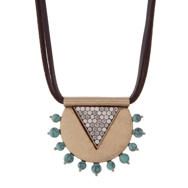 """Brown leather necklace featuring a burnished gold tone pendant accented with clear rhinestones and turquoise stones. Approximately 32"""" in length."""