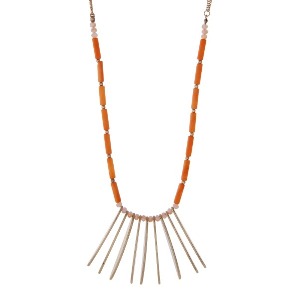 "Gold tone necklace featuring metal fringe, accented with champagne and orange colored beads. Approximately 32"" in length."