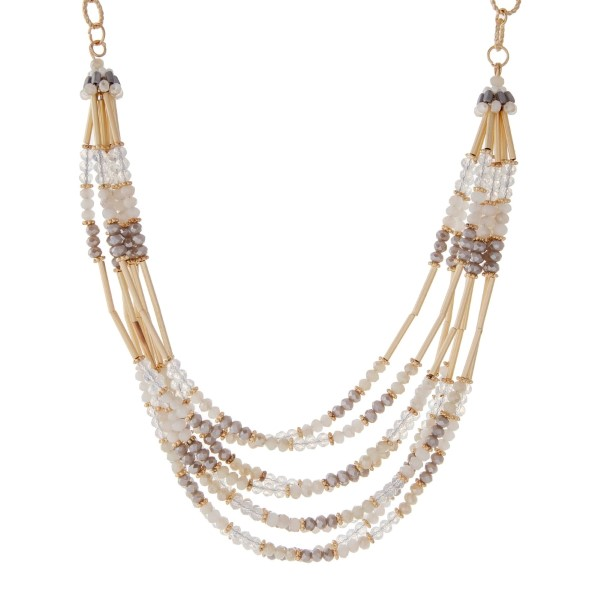 """Gold tone necklace featuring multiple rows of white and gray beads with gold hardware. Approximately 16"""" in length."""
