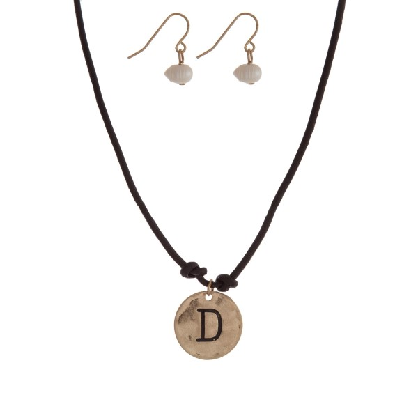 """Brown cord necklace with a gold tone pendant stamped with the letter """"D"""" and a pearl closure. Approximately 18"""" in length."""