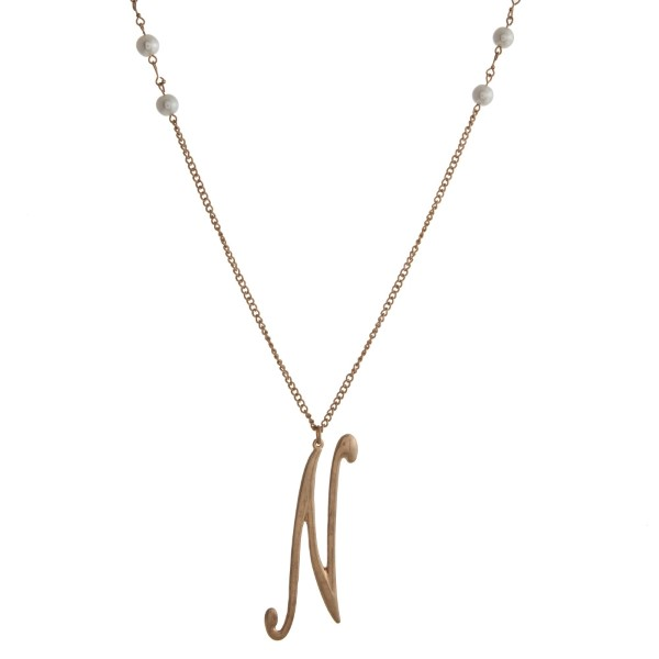 "Gold tone necklace with white pearl beads and a script 'N' initial pendant. Approximately 36"" in length."