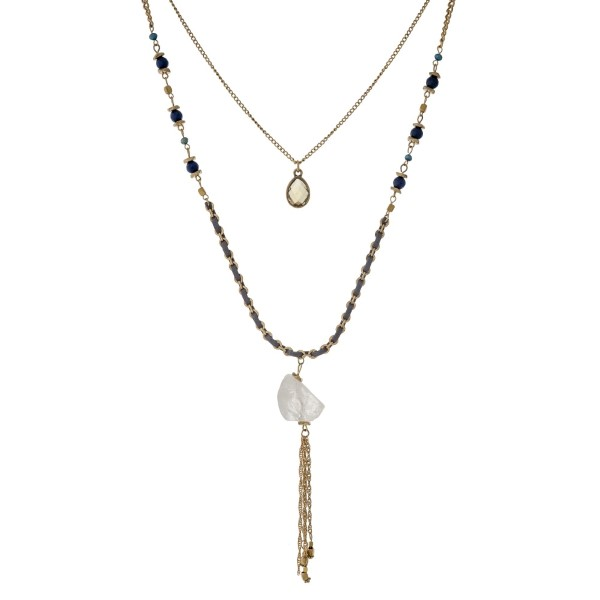 """Burnished gold tone double layer necklace with navy blue beads, gray thread, a white crystal pendant, and a chain tassel. Approximately 32"""" in length."""