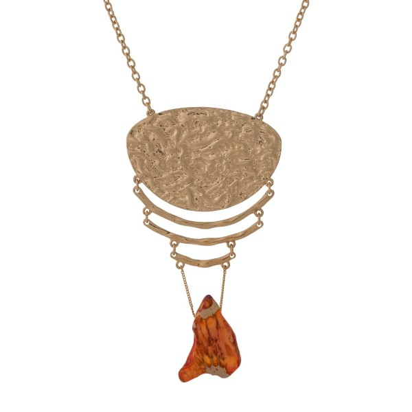 "Gold tone necklace with a hammered pendant and an orange natural stone. Approximately 32"" in length."