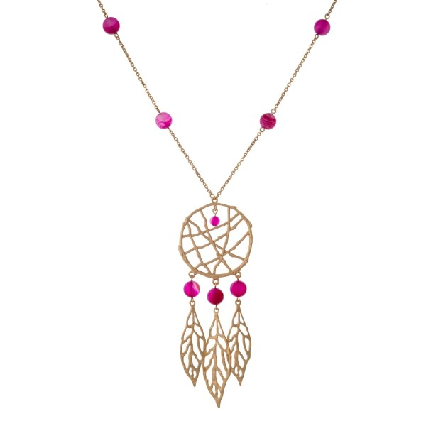"Gold tone necklace with fuchsia beads and a dream catcher pendant. Approximately 32"" in length."