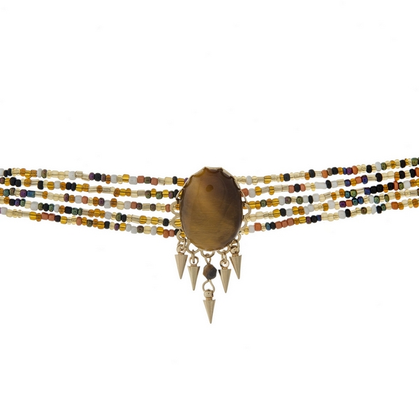 "Multi row beaded choker with a brown faceted stone focal and gold tone accents. Approximately 12"" in length."