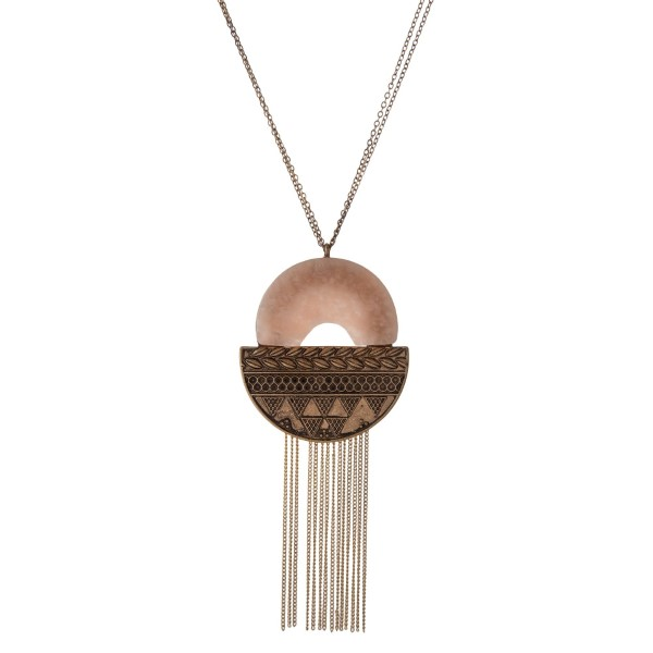 """Burnished gold tone necklace with a tribal pendant, accented with a neutral natural stone and metal fringe. Approximately 32"""" in length."""