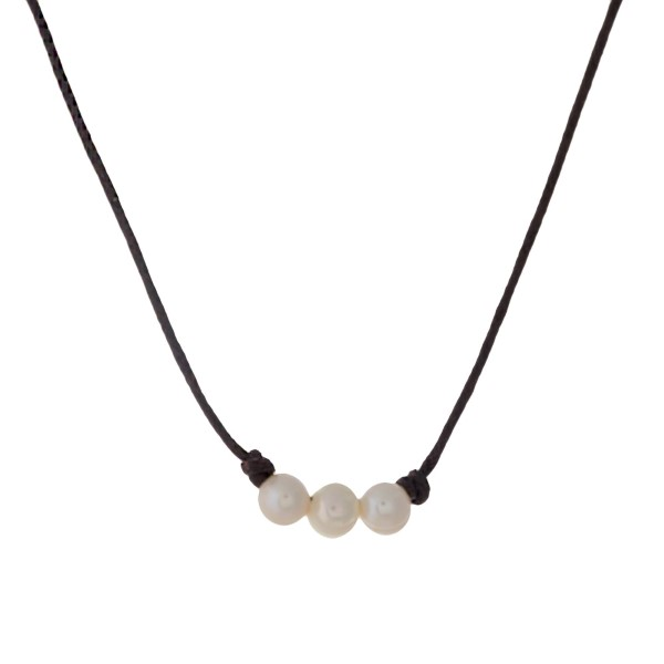 """Brown waxed cord necklace with three cream freshwater pearl beads. Approximately 16"""" in length."""