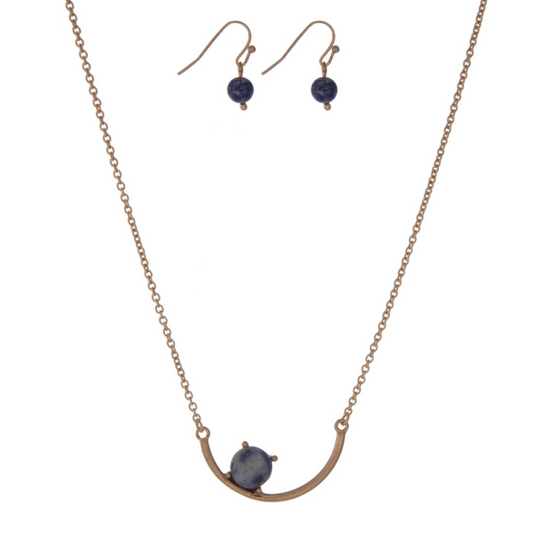 "Dainty gold tone necklace set with a curved bar pendant accented with a blue stone. Approximately 16"" in length."