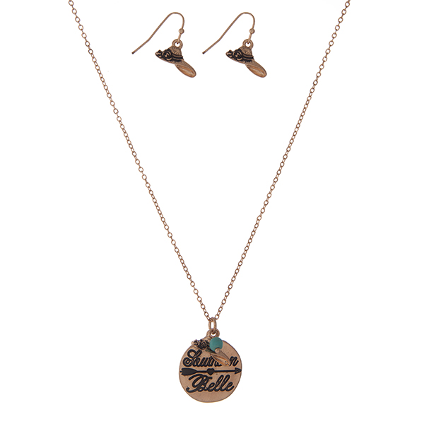 """Dainty gold tone necklace set with a circle pendant stamped with """"Southern Belle"""" and accented with a turquoise bead and matching fishhook earrings. Approximately 16"""" in length."""