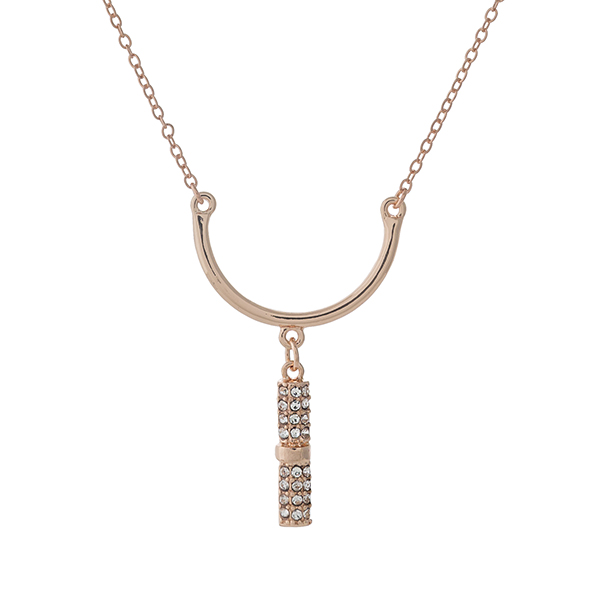"Dainty rose gold tone necklace set with a curved bar pendant and clear rhinestone accents. Approximately 16"" in length."