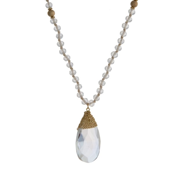 """Clear beaded necklace with gold tone accents and a teardrop shaped pendant. Approximately 32"""" in length."""