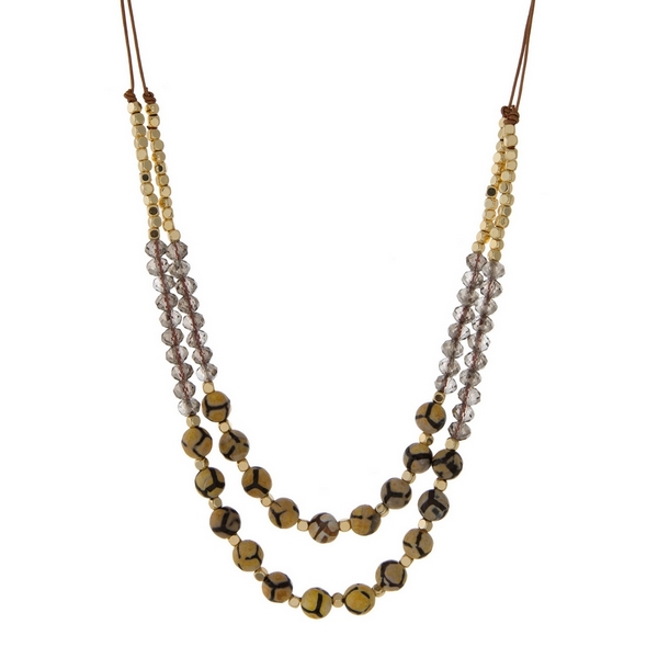 """Brown cord necklace with gold tone, gray, and black natural stone beads. Adjustable from 14"""" to 27"""" in length. Handmade in the USA."""