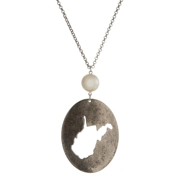"""Burnished silver tone necklace with a West Virginia cutout pendant accented by a pearl bead. Approximately 30"""" in length. Oval pendant is approximately 2.5"""" tall."""