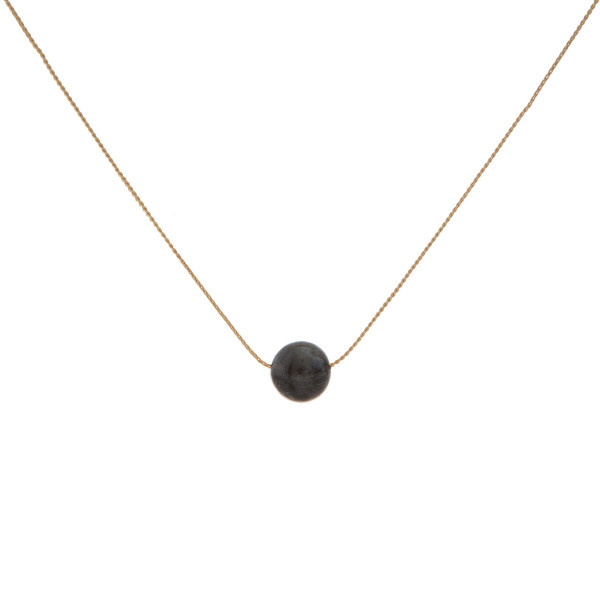 "Dainty gold tone necklace with a natural stone bead pendant. Approximately 16"" in length. Natural stone colors may vary."