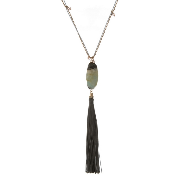 "Gold tone and pink cord necklace displaying a jet amazonite natural stone pendant and a gray tassel. Approximately 32"" in length."
