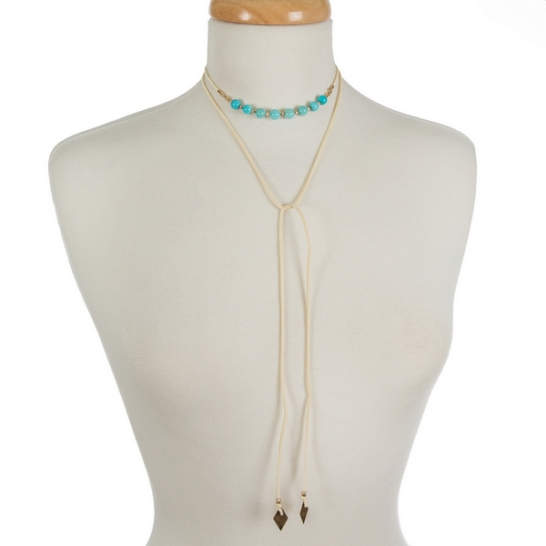 "Ivory faux suede wrap choker featuring turquoise beads. Approximately 12"" in length."