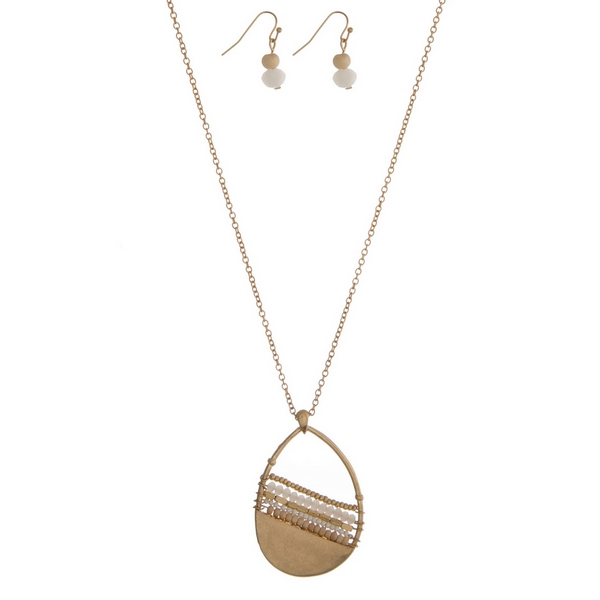 """Gold tone necklace set featuring a white beaded teardrop pendant and matching fishhook earrings. Approximately 32"""" in length."""