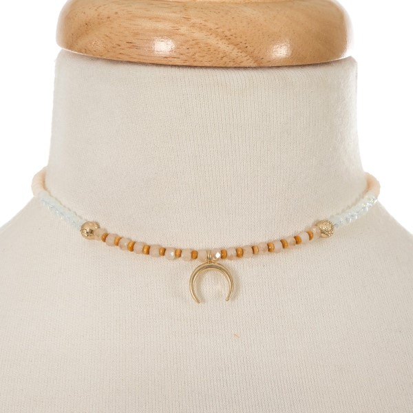 "Ivory and opal beaded choker with a gold tone crescent pendant. Approximately 12"" in length."