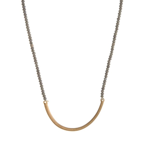 "Gold tone and gray beaded necklace with a curved bar pendant. Approximately 30"" in length."