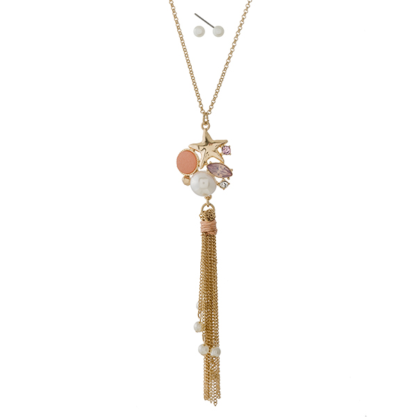 "Gold tone necklace set with a seashell, peach rhinestone, and tassel pendant. Approximately 22"" in length."