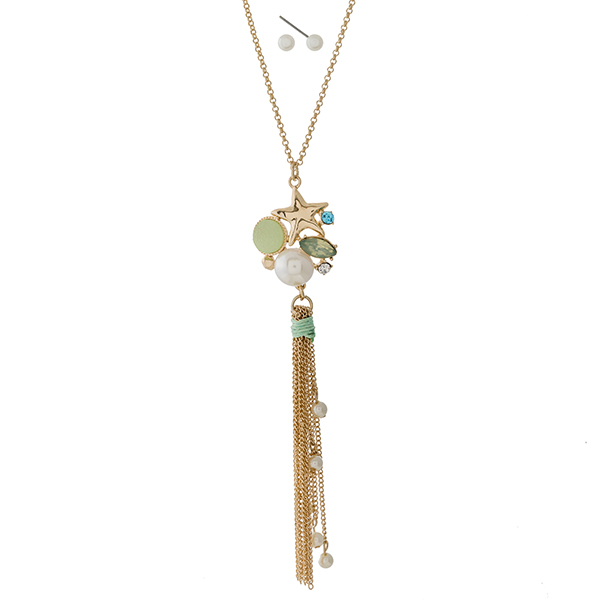 "Gold tone necklace set with a seashell, mint green rhinestone, and tassel pendant. Approximately 22"" in length."