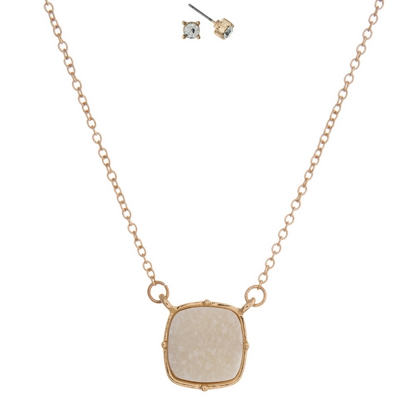 "Gold tone necklace set with an ivory faux druzy stone pendant and matching stud earrings. Approximately 16"" in length."