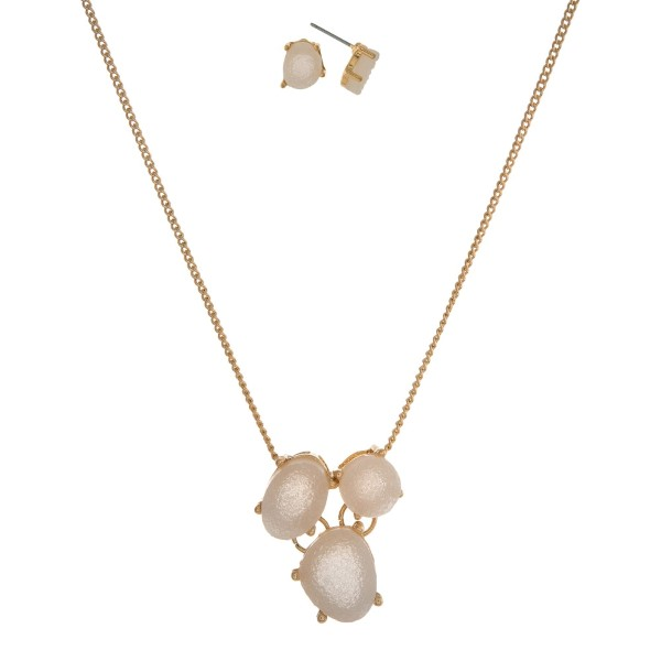 """Gold tone necklace set with a white faux druzy pendant and matching stud earrings. Approximately 16"""" in length."""