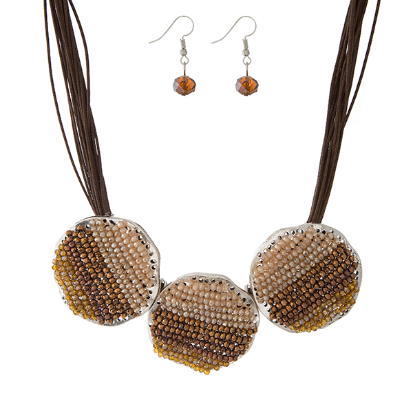 "Brown waxed cord necklace set with three brown and topaz beaded circles, and matching fishhook earrings. Approximately 16"" in length."