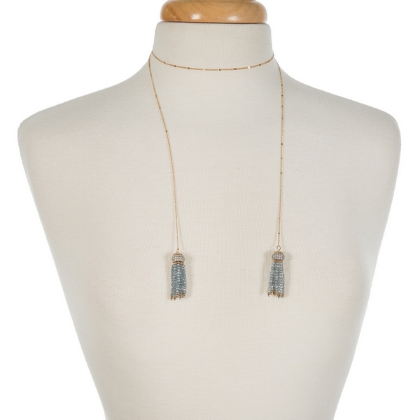"Gold tone lariat necklace with two, light blue beaded tassels. Approximately 40"" in length."
