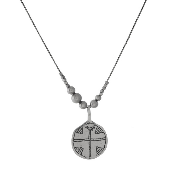 "Silver tone necklace with a circle pendant, stamped with a cross. Approximately 30"" in length."