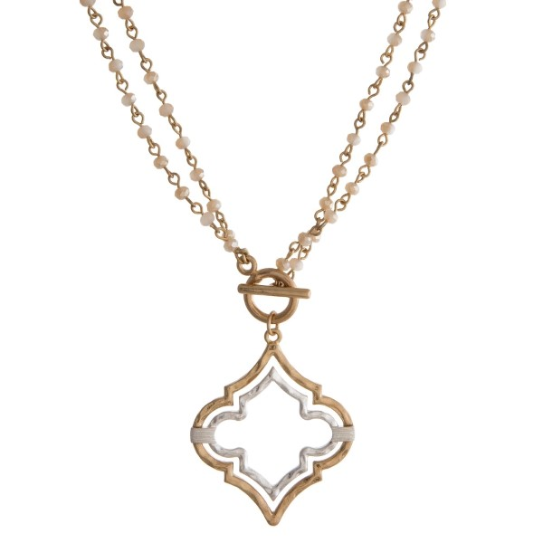 """Gold tone necklace with a two tone, hammered quatrefoil pendant and a front toggle closure. This necklace can be worn as an 18"""" or 36"""" necklace."""