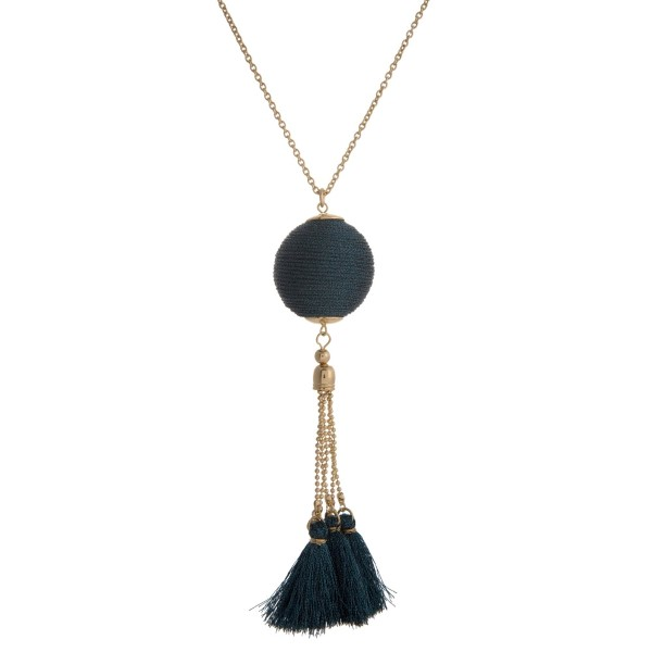 """Gold tone necklace with a metallic navy blue thread wrapped pendant and thread tassels. Approximately 30"""" in length."""