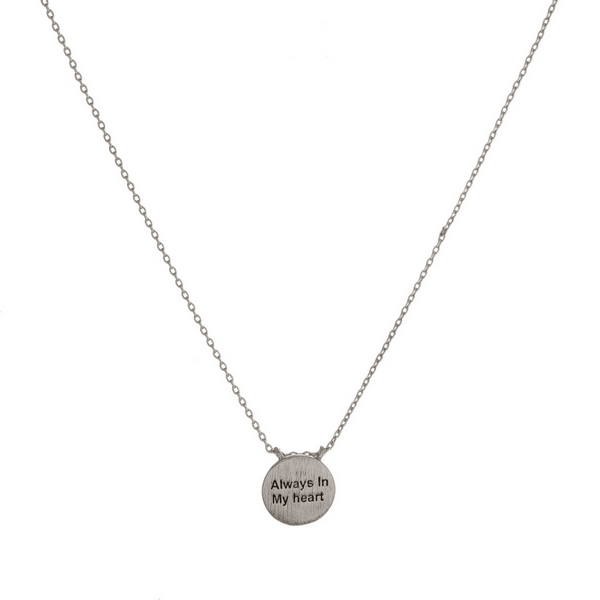 "Dainty metal necklace with a circle pendant, stamped with ""Always in My Heart."" Approximately 16"" in length."