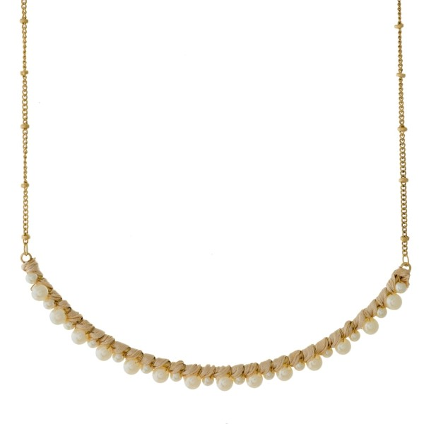 "Gold tone necklace with a curved bar pendant and wire-wrapped pearl beads. Approximately 15"" in length."