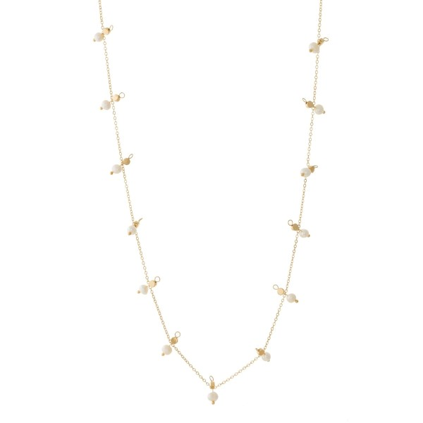 "Dainty gold tone necklace with pearl beaded accents. Approximately 32"" in length."