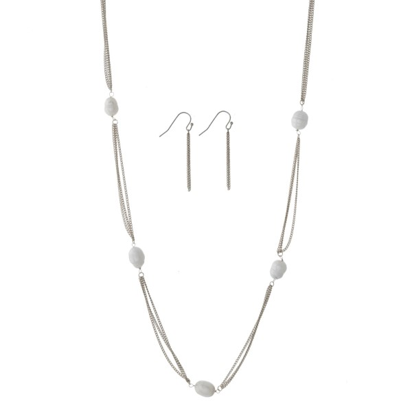 "Long, metal necklace set with freshwater pearl beads and matching fishhook earrings. Approximately 36"" in length."