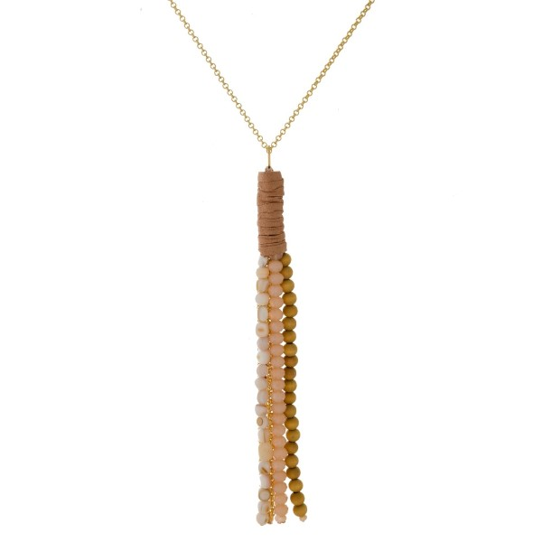 """Gold tone necklace with a wooden, faceted, and natural stone beaded tassel pendant with suede wrapping accents. Approximately 32"""" in length."""