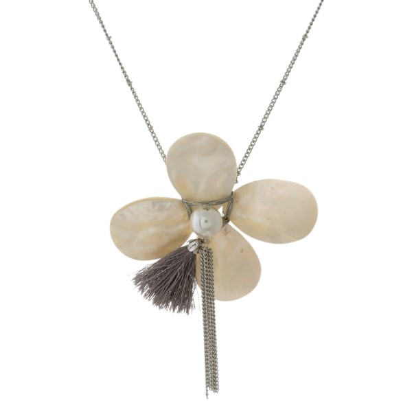 "Silver tone necklace with a mother of pearl flower pendant. Approximately 30"" in length."