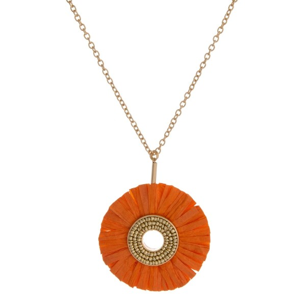"Gold tone necklace with a raffia circle pendant. Approximately 32"" in length."
