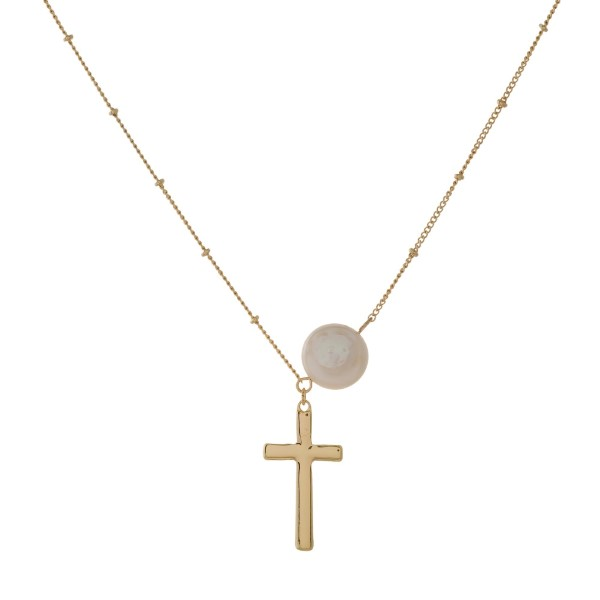 "Dainty metal necklace with a freshwater pearl bead and a cross pendant. Approximately 16"" in length."