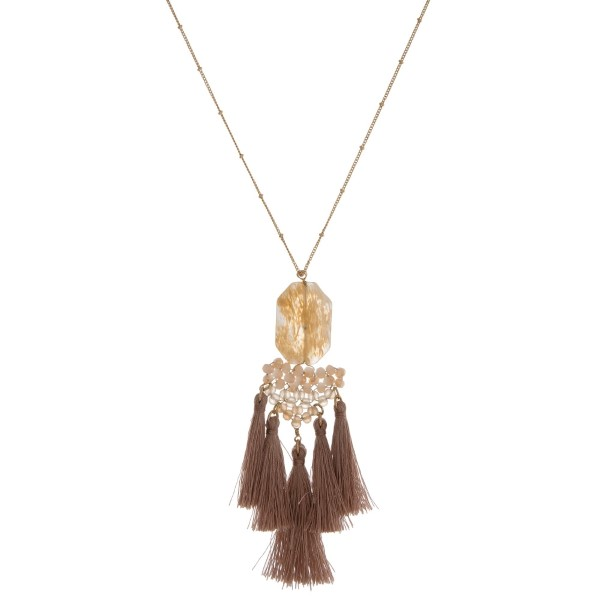 """Gold tone necklace with a natural stone pendant, beaded accents and tassels. Approximately 32"""" in length."""