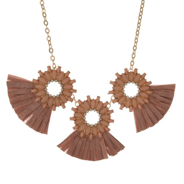 "Gold tone, statement necklace with rhinestone details and raffia fans. Approximately 18"" in length."