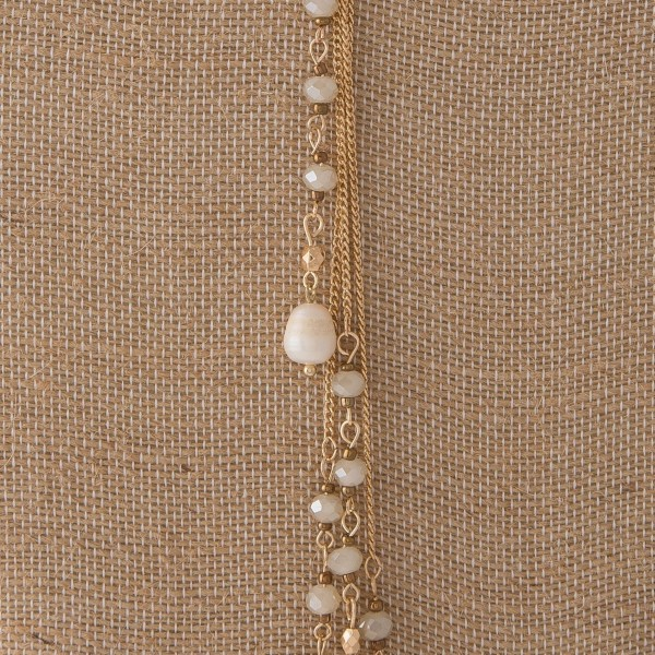 "Gold tone Y necklace with freshwater pearl and faceted beads. Approximately 20"" in length."