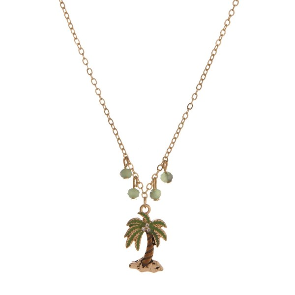 "Gold tone necklace with palm tree pendant and faceted beads. Approximately 16"" in length."