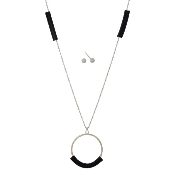 """Long, metal necklace with circle pendant and leather accent. Gold stud earrings. Approximately 24"""" long."""