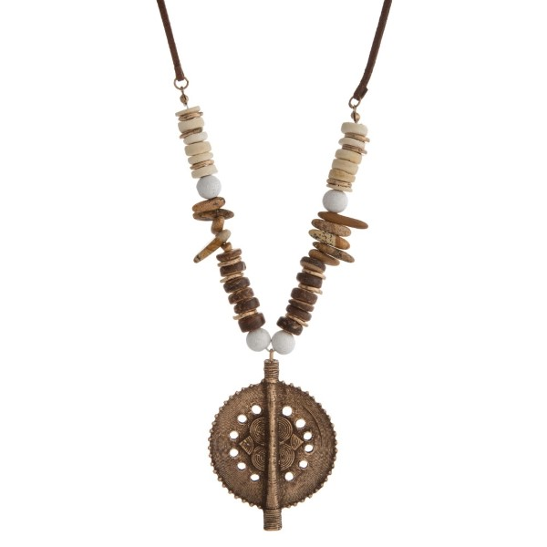 """Faux suede cord necklace with wooden beads, natural stone beads and a burnished metal boho pendant. Approximately 36"""" in length."""